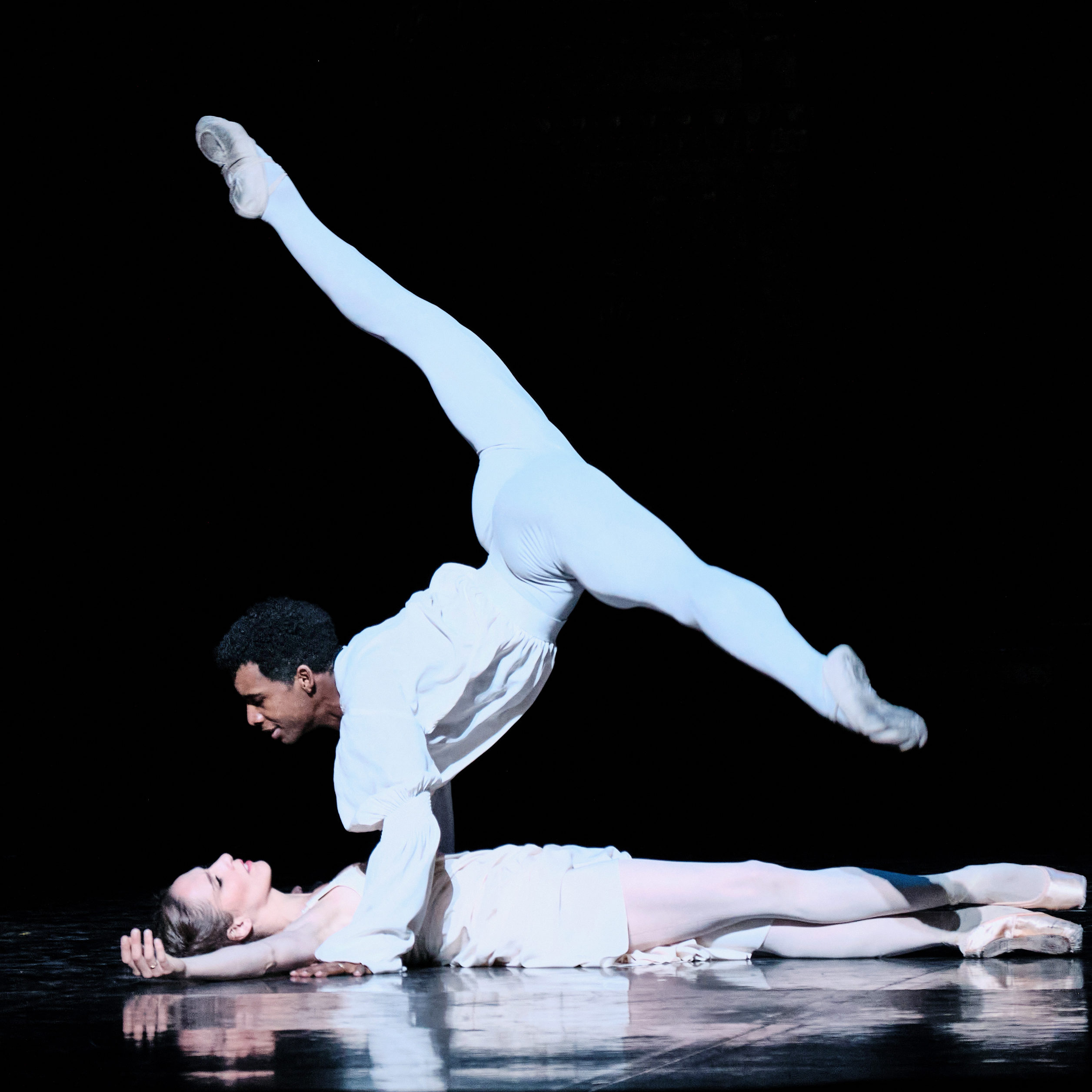 Osiel Gouneo and Valentine Colasante, in white costumes, perform onstage. Gouneo is in a split position balanced on his hands, looking at Colasante, who is lying on the stage beneath him.