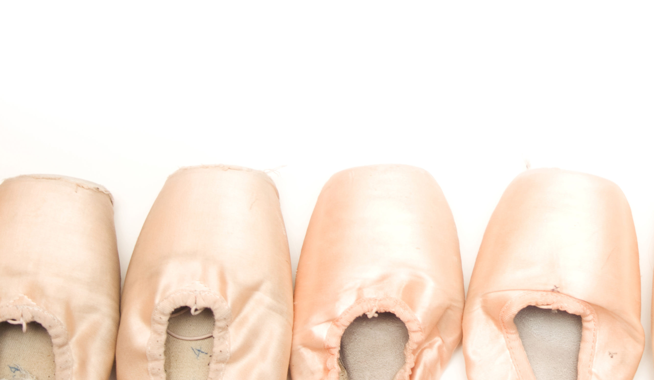 A photo of pointe shoes lined up on a white background.