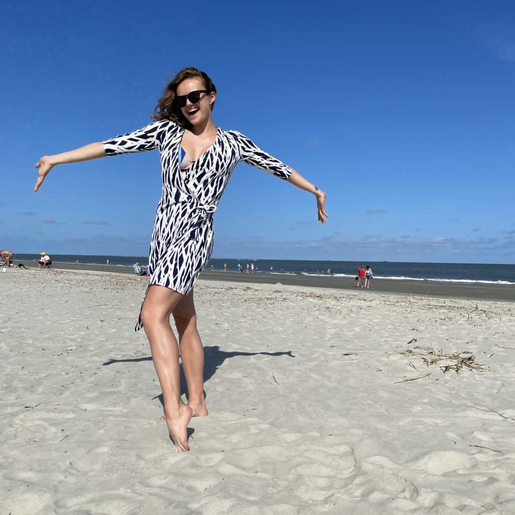 Abbey Marrison stands on a beach with her arms out, her left leg beveled and a huge open-mouth smile. She wears a black-and-white patterned wrap-dress and sunglasses.