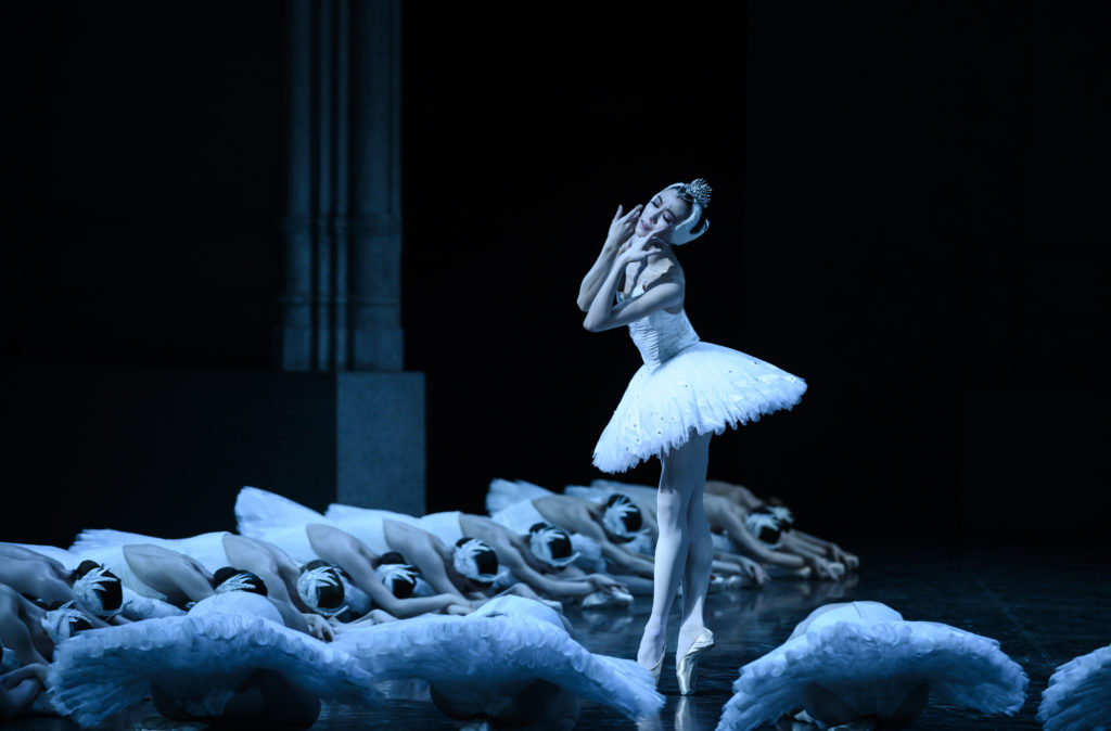 Sae Eun Park, dressed in costume as Odette/Odile in a white tutu and feathered tiara, bourreés in fifth and touches the sides of her face in anguish. A group of corps de ballet dancers poses on the ground around her.