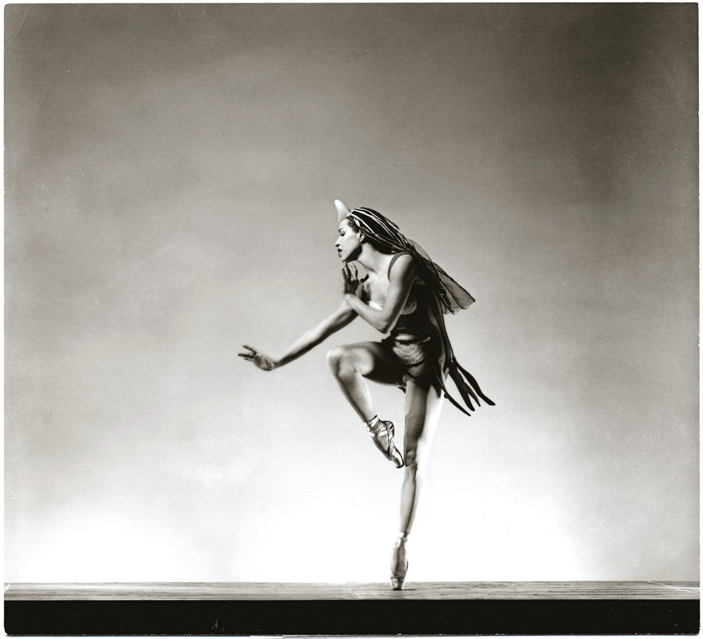 In this black and white photo, Maria Tallchief performs a parallel retiré with her right leg, her left foot on pointe. She reaches her right arm forward with a flexed wrist and looks out over it while reaching her left hand up towards her face. Tallchief wears a long veil-like headpiece and a leotard with knit circles sewn onto it.