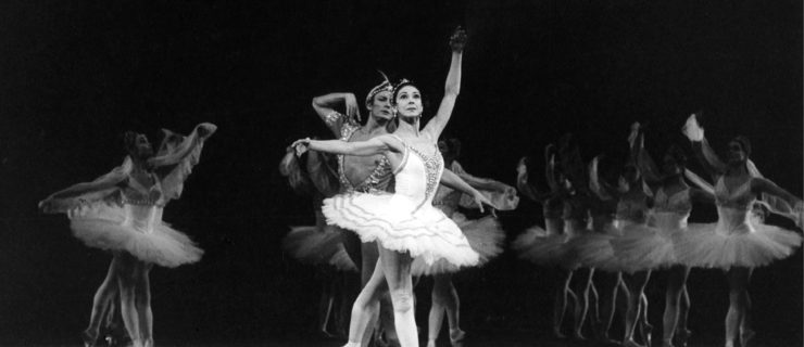 """A black and white photo of Margot Fonteyn standing at the front of the Royal Opera House stage. She wears a white tutu and looks out into the audience with her arms in fourth position and her back leg pointed. Behind her is Keith Rosson, her partner for """"La Bayadere,"""" and three columns of corps de ballet dancers all in the same position as her."""