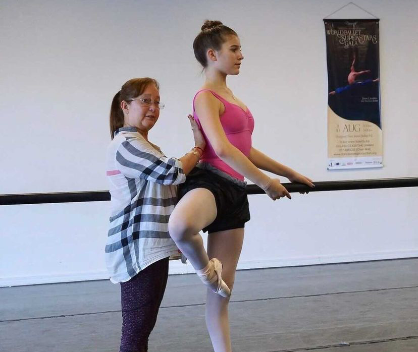 Magaly Suárez, wearing a long-sleeved blouse and leggings, presses her right hand against Suttyn SImon's back to correct it while she balances in retiré. Suttyn wears a pink leotard, pink tights and pointe shoes, and a black skirt.