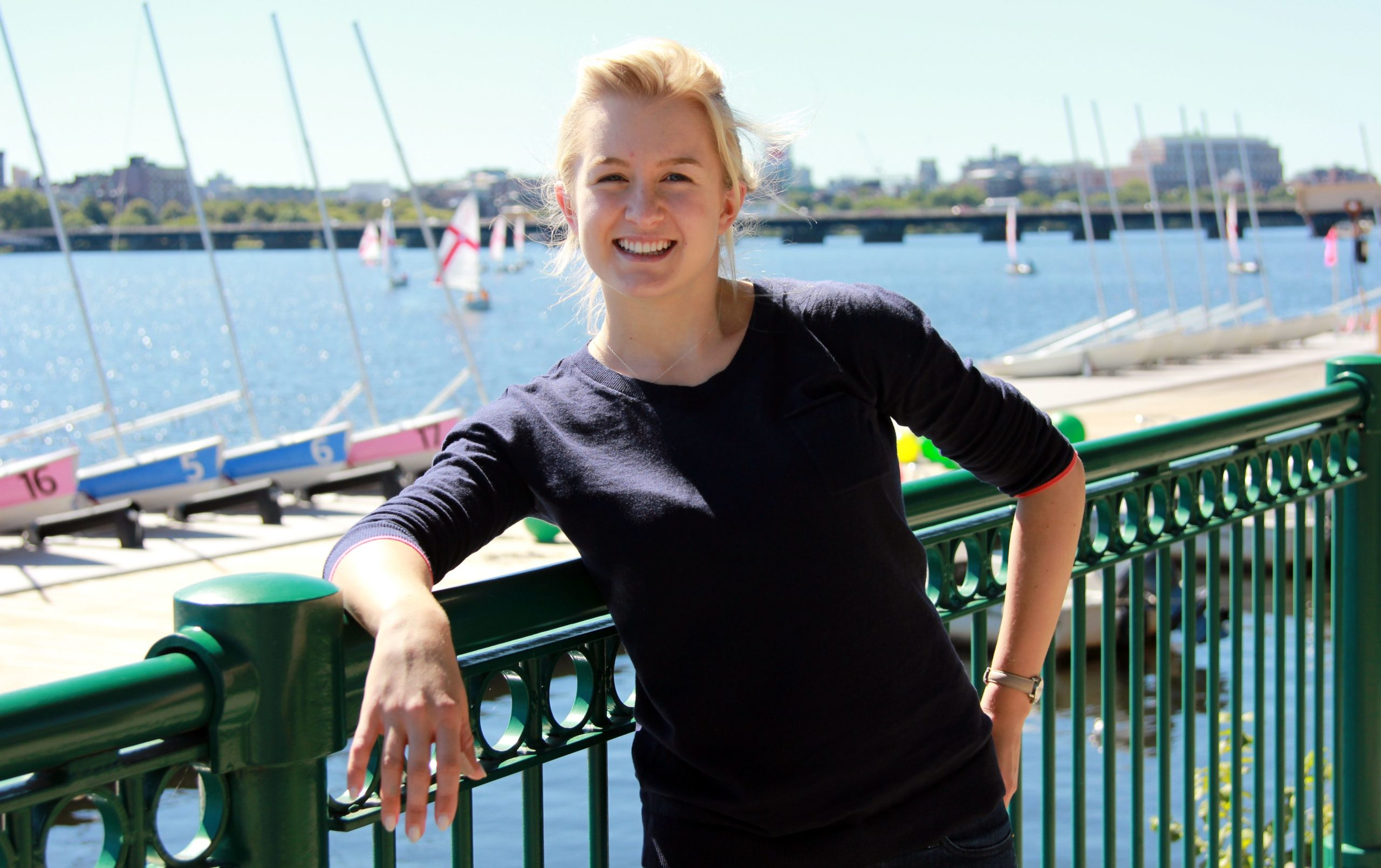 Grace Young, wearing a dark, long-sleeved Tshirt, leans against a railing at a marina and smiles cheerfully at the camera. Behind her is a river with several small sailboats.