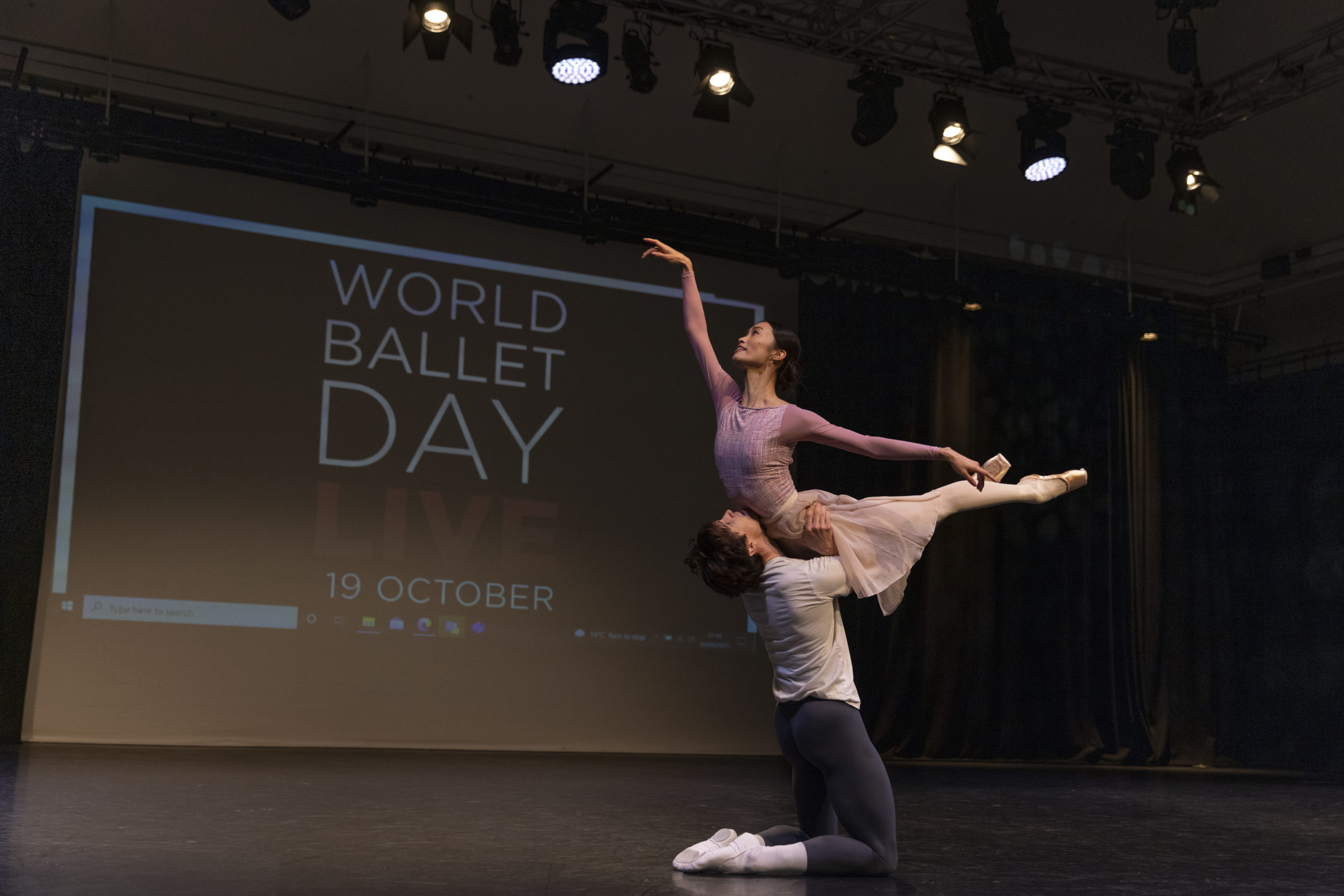 William Bracewell, kneels on the ground and holds Fumi Kaneko overhead by the hips as she arches her upper body up and lifts both her legs behind her. Both wear dance clothing and dance onstage in front of a backdrop that says World Ballet Day LIVE 19 October.
