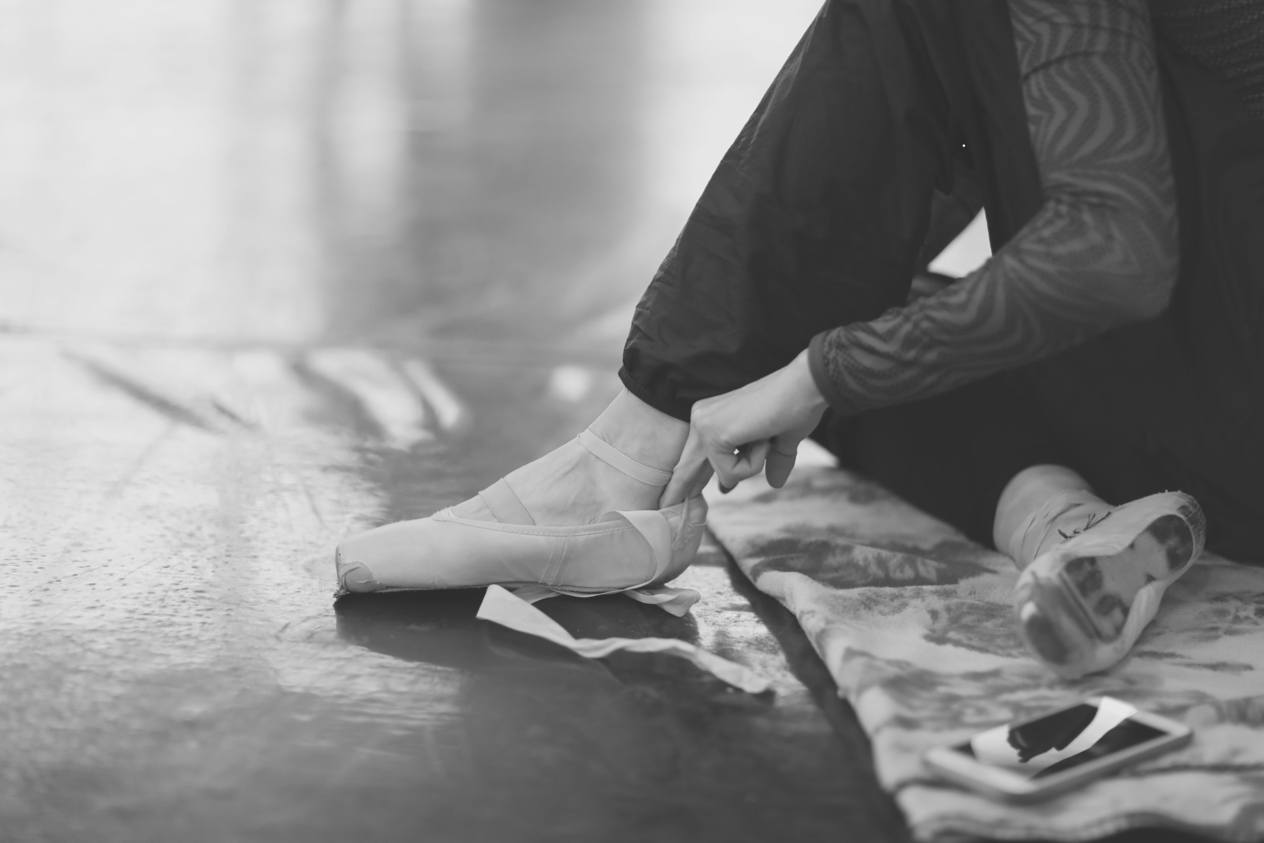 A ballerina sits on the floor in the theater's rehearsal hall and puts on pointe shoes.