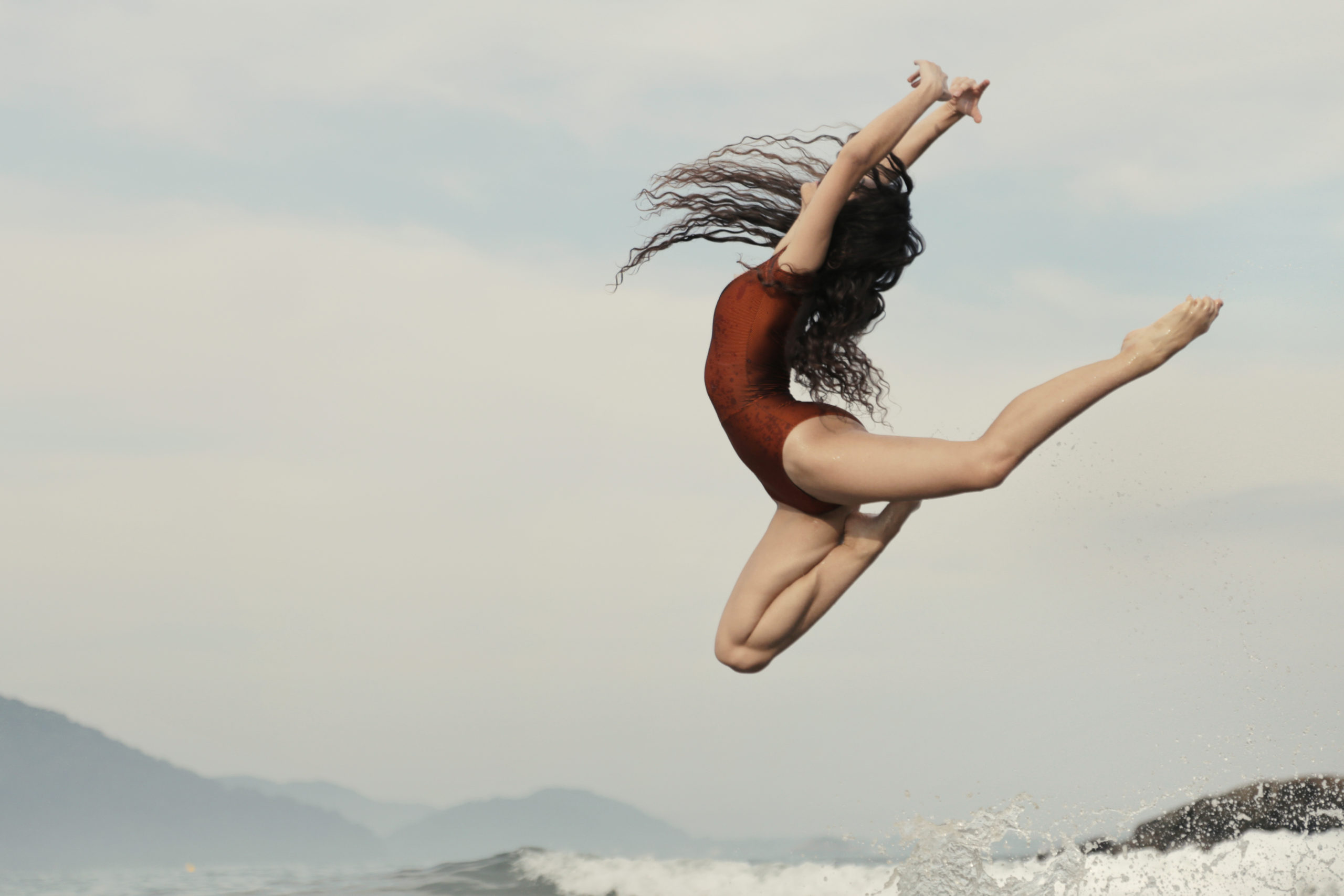 A ballerina in a bronze-colored leotard jumps in the ocean, tucking her right leg up and her kicking back leg in attitude. She arches back with her arms in high fifth and her with long, curly hair flying free.