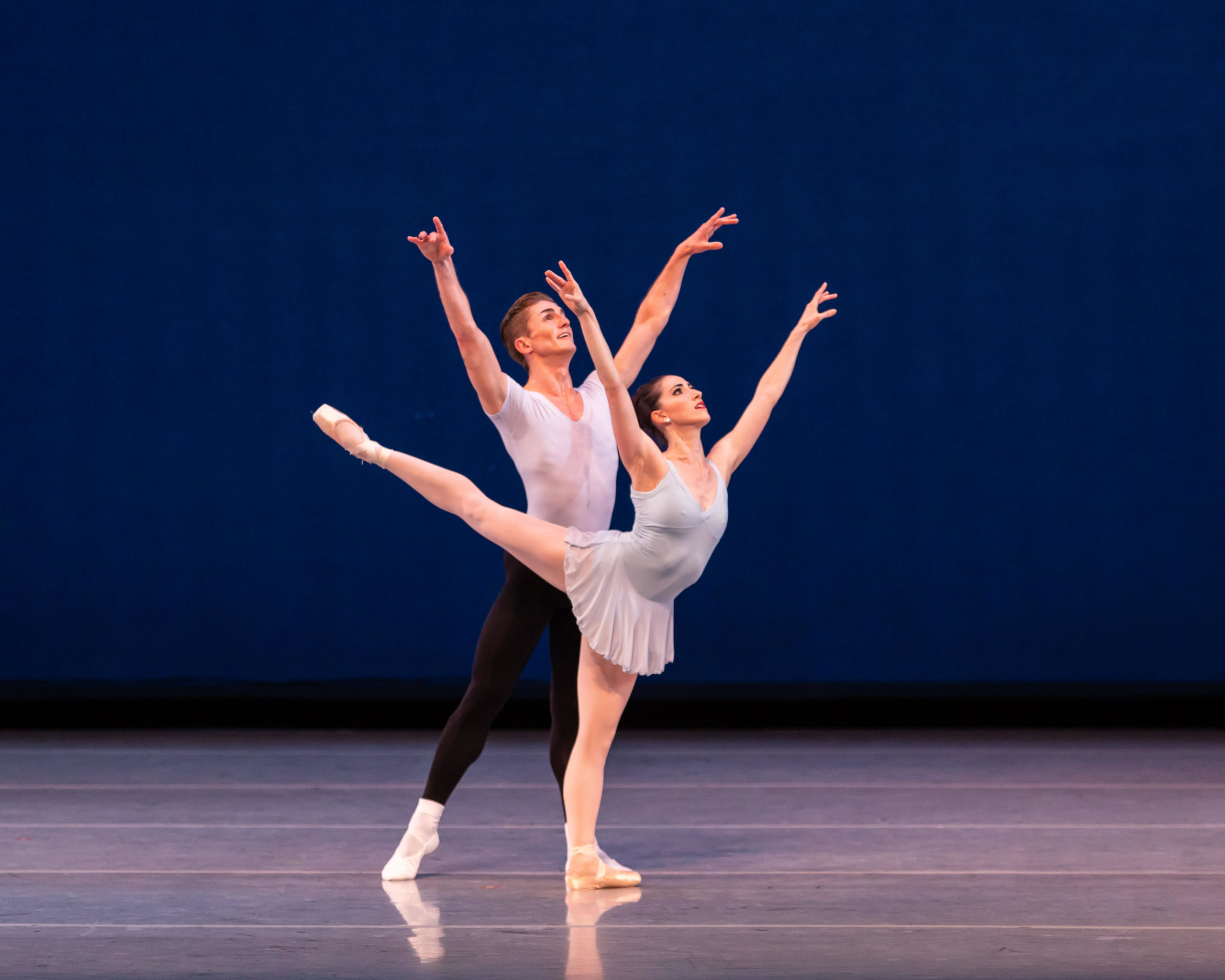Julia Eisen stands onstage in a blue leotard and short chiffon skirt. She holds an arabesque on flat with her arms in open fifth. Behind her, Nicolas Scheuer reflects the position, also with his arms in open fifth, and both his feet on the ground.