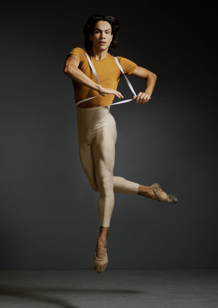 Esteban Hernández does a small jump off of his left foot, lifting his bent right leg behind him. He wears a gold T-shirt, beige tights and tan ballet slippers.