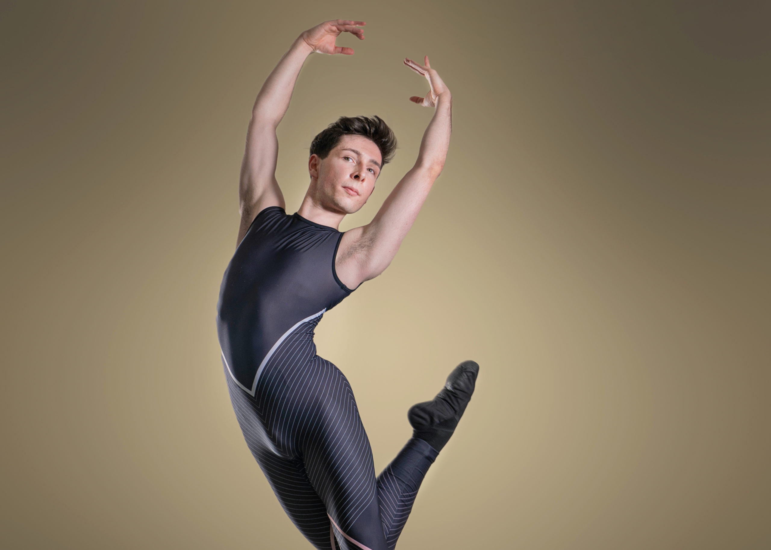 Wearing a dark, patterned unitard, Ballet Jörgen dancer Callum McGregor jumps into the air with his right leg tucked behind him and his arms in fifth position.