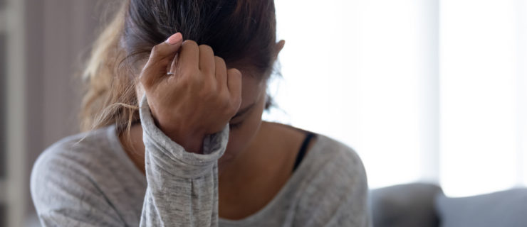 A young woman in a gray shirt is shown from the chest up, holding her right hand to her head in despair.