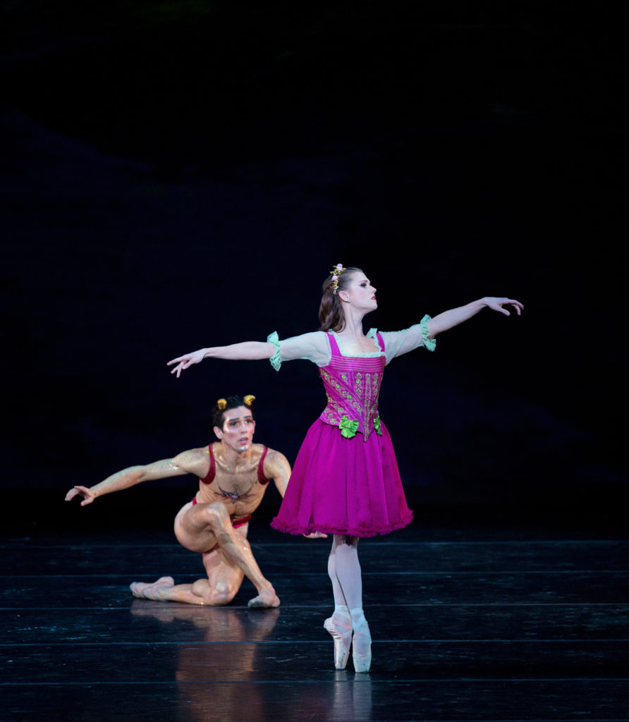 Abby Phillips Maginity stands onstage in sus-sous croisé on pointe, stretching our her arms and looking out over her left hand. She wears a fuchsia costume of a peasant dress and flowers in her hair. Behind her, a male dancer crouches wearing a Puck costume.
